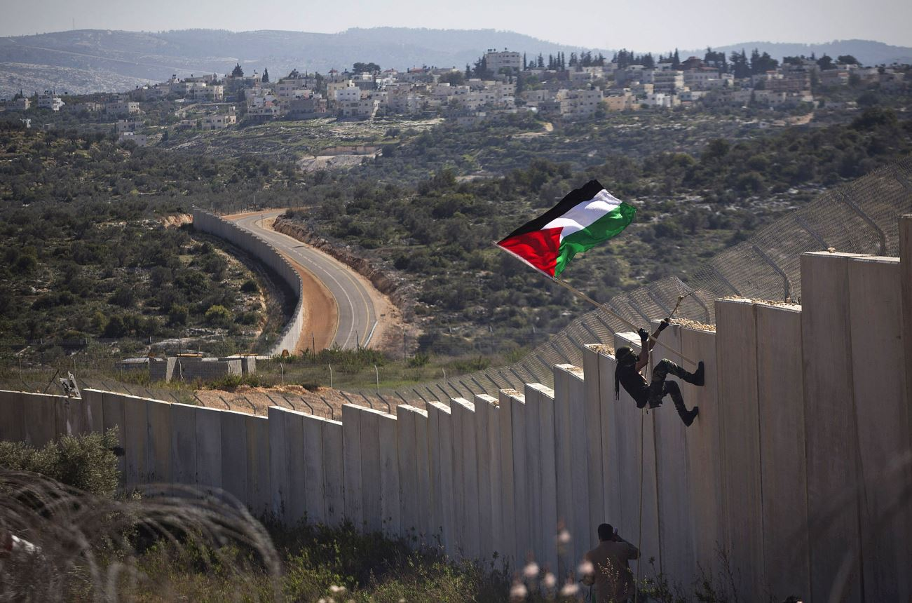 Palestinian protest climbing West Bank separation wall with flag